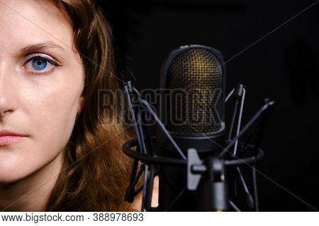Professional Record Of The Singer, Close-up. Female Vocalist On Black Background In Recording Studio