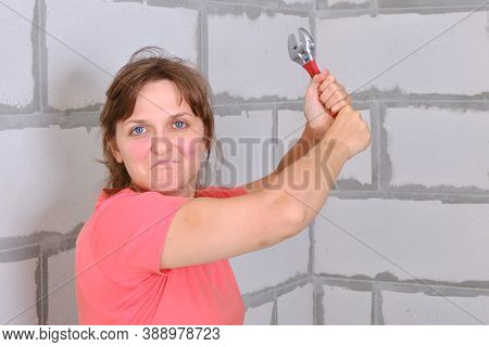 A Young Woman Swings A Red Wrench. The Woman With Anger In His Eyes Preparing To Attack In Self-defe