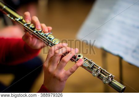 Woman Is Holding A Large Concert Flute (in Hands Close-up). Professional Musician At The Rehearsal.