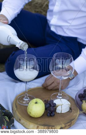 Mans Hand Pouring Champagne In Glass On Wooden Stand With Grapes And Camembert Cheese On A White Bla