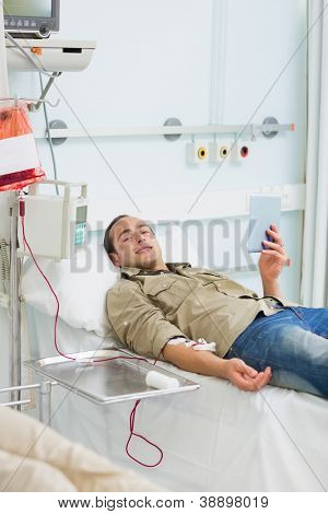 Male transfused holding a tablet computer in hospital ward