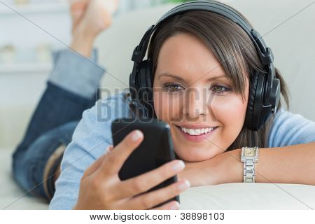 Woman using her smartphone and listening to music on sofa in the living room