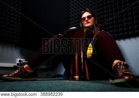 A Woman Sits On The Floor Of A Music Studio And Plays An Ethnic African Drum Darbuka. Professional R