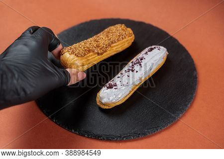 Raspberry Eclair And Caramel Eclair Held By Hand In Black Glove On Round Black Rock Stand. Eclairs W