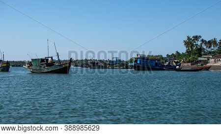 Several Traditional Wooden Boats In A River And Houses On The Shore In Front Of Palm Trees By The Fi
