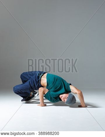Young Guy Breakdancer Dancing Lower Break Dance Isolated On Gray Background. Break Dance Lessons