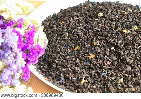 Ceylon Tea And Cornflower Petals, Close-up. Dry Tea Leaves On A White Plate. Dried Flowers Of White