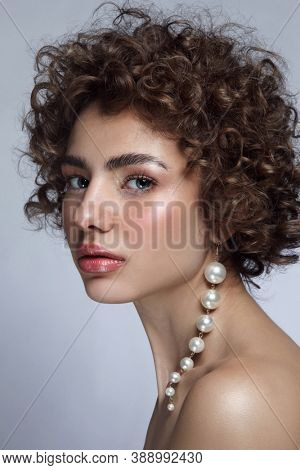 Portrait of young beautiful woman with curly hair and fancy pearl earring