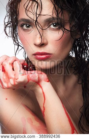Portrait of young beautiful woman squeezing juicy cherries in her hand