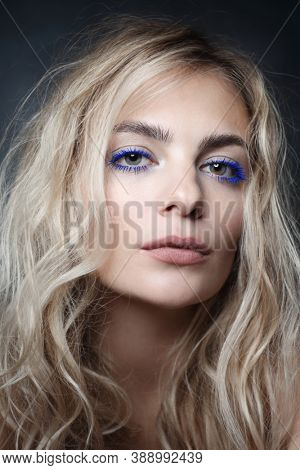 Portrait of young beautiful woman with blue mascara