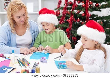 Family around christmas time making greeting cards wearing santa hats