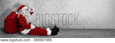 Sitting Santa Claus With A Bag. Christmas and New Year Concept
