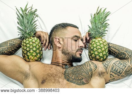 Muscular Man Hold Pineapple Fruit On Biceps. Brutal Sportsman Relax In Bed. Steroids. Sexy Ab Of Tat