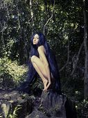Beautiful nude lady with magnificent hair in a tropical forest poster