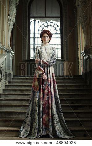 beautiful woman in elegant dress posing on stairs in old vintage interior