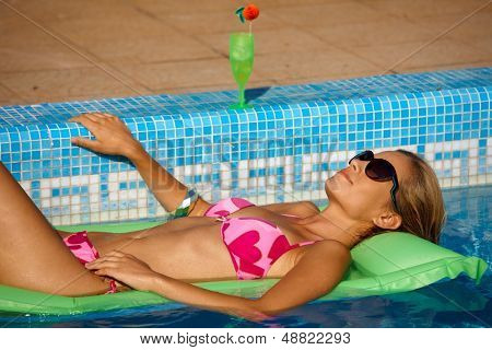 Young woman laying on airbed in swimming pool, enjoying summer holiday.