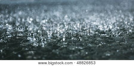 Drops of heavy rain on water