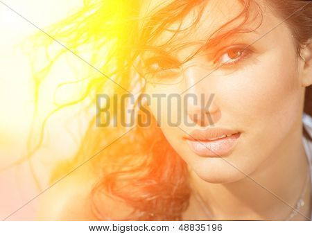 Beauty Sunshine Girl Portrait. Happy Woman Smiling and looking at Camera. Sunny Summer Day under the Hot Sun on the Beach.