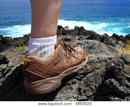A foot of a hiker standing on a lava coast of Easter Island poster