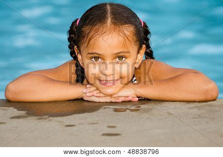 Portrait of happy pretty mixed race child by side of pool during summer