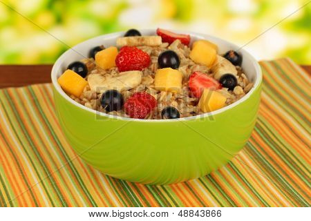 Oatmeal with fruits on table on bright background