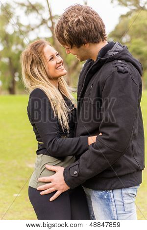 Cheerful young couple hugging and smiling in a park