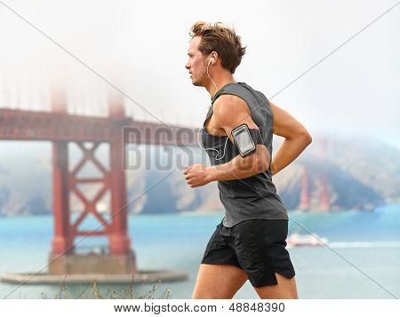 Running man - corredor masculino em San Francisco, ouvindo música no telefone inteligente. J ajuste desportiva jovem