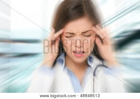 Migraine and headache people - Doctor stressed. Woman Nurse / doctor with migraine headache overworked and stressed. Health care professional in lab coat wearing stethoscope at hospital.