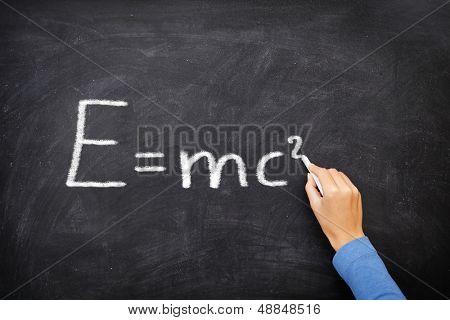 physics science formula equation blackboard, E=mc�². EMC2 written on chalkboard by science teacher or student in class.
