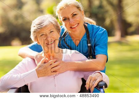 happy senior woman in wheelchair outdoors with caring caregiver