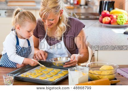Baking with the family - Mother and daughter coat self made cookies with a brush