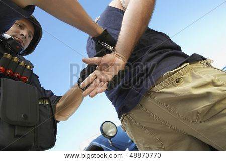 Low angle view of policeman arresting criminal against sky poster