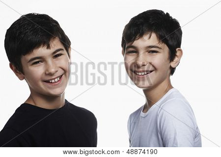 Closeup portrait of happy preadolescent brothers isolated over white background