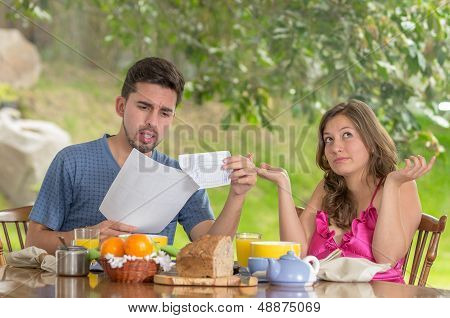 couple having breakfast fighting over bills at home with garden in the background