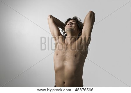 Barechested young man stretching against gray background