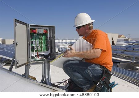 Electrical engineer holding book while analyzing electricity box at solar power plant