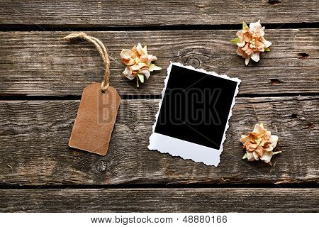 Instant photo frame with gift tag and craft flowers on old wooden background.
