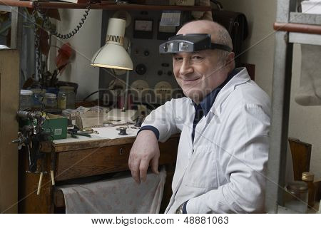 Portrait of smiling senior watch repairman in workshop