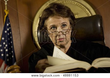 Middle age female judge with book looking away in court room