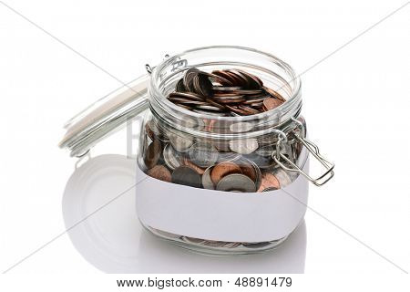 Closeup of a mason jar filled with assorted coins. Lid is open and a blank label ready for your own text surrounds the container.