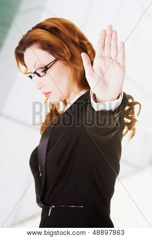 Serious business woman gesturing stop sign