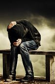 Man with problems. Man in hood with hands on his head sitting on the concrete bench. Drug addict concept. poster