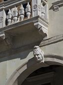 Detail of a Renaissance facade funny face with emotional expression. Tongue out. poster