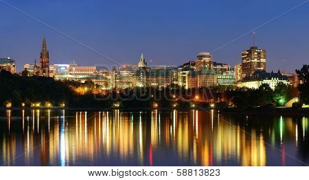 Ottawa at night over river with historical architecture.