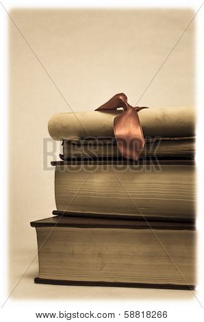 Pile Of Books And Diploma Scroll