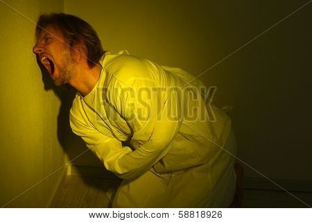 Mentally ill man in strait-jacket in room corner poster