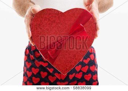 Man in hear underwear holding a big red Valentines Day heart filled with chocolate candy.  White background.