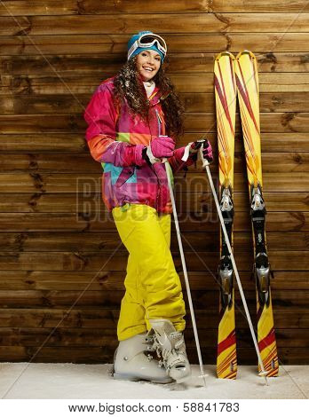 Smiling woman with skies and poles standing against wooden house wall on a snow
