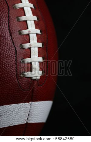 American Football Close Up against Black Background with room for copy