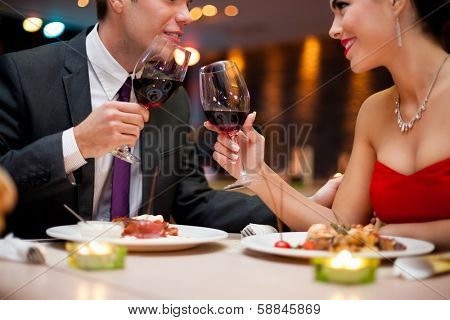 hands of couple toasting their wine glasses over a restaurant table during a romantic dinner.